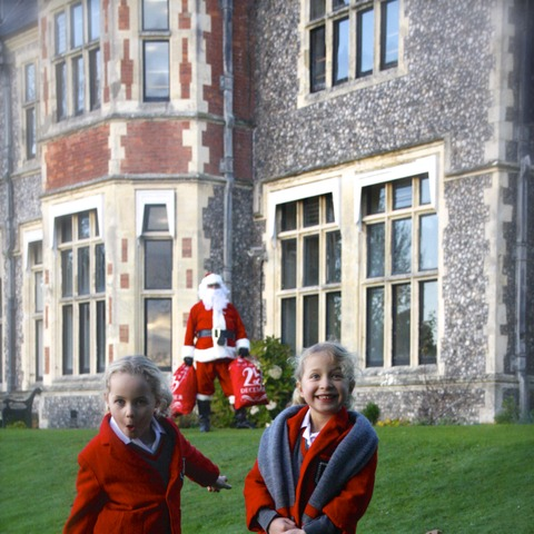 Delighted children spot Santa in the school grounds