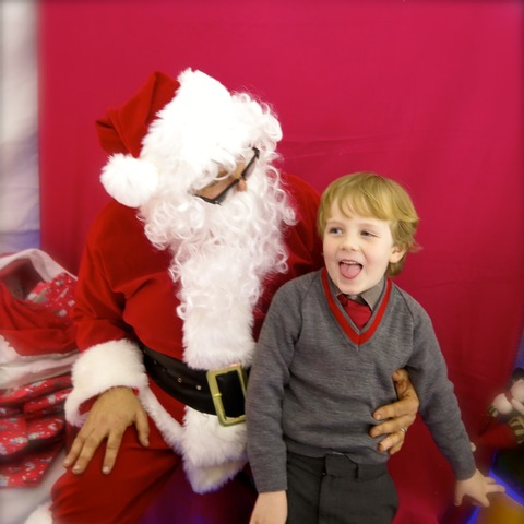 Santa in his Grotto with a happy Pre-Prep pupil