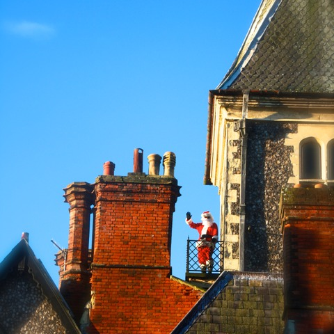 A rare sighting of Santa beside the chimneys on the roof of the Neo-Gothic Sompting Abbotts Prep School building
